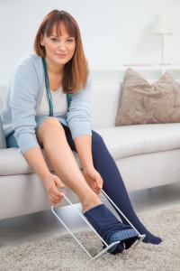 Frau mit medi Butler - Anziehhilfe für Kompressionsstrümpfe